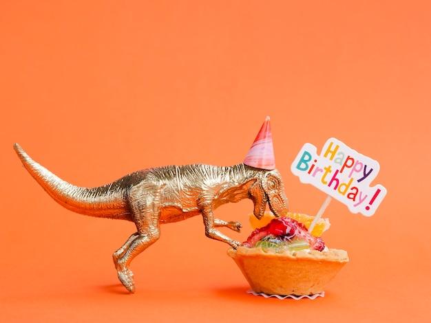 Dinosaurio de juguete comiendo dulces de cumpleaños