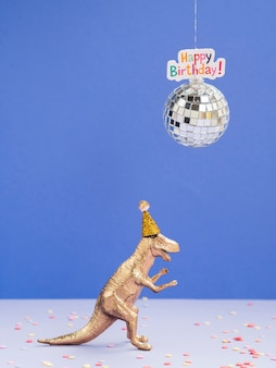 Dinosaurio de juguete con gorro de cumpleaños y globo de discoteca