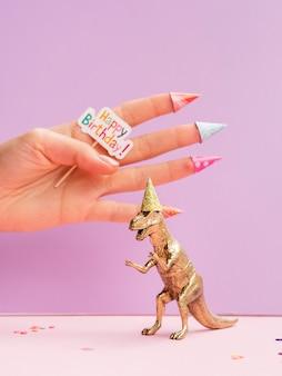 Dinosaurio de juguete y mano con cartel de feliz cumpleaños