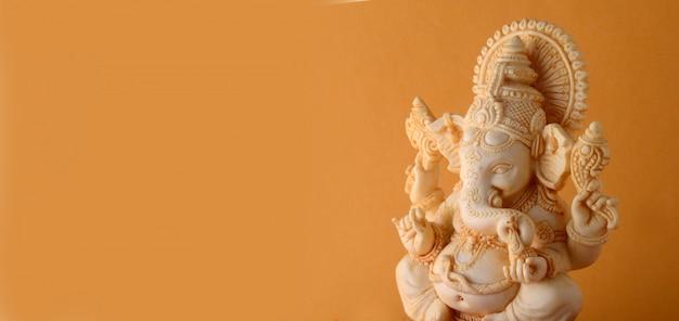 Dios hindú ganesha idol sobre superficie amarilla