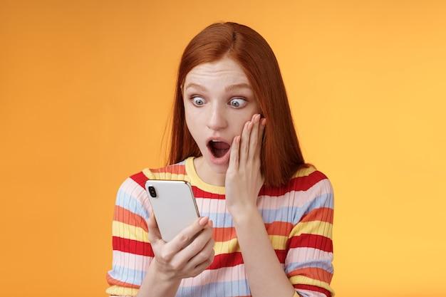 Dios mío, qué diablos. retrato conmocionado preocupado joven pelirroja sensible impresionado mujer pelirroja mirada teléfono inteligente pantalla toque mejilla caída mandíbula aturdido sorprendido permanente fondo naranja mantenga teléfono.