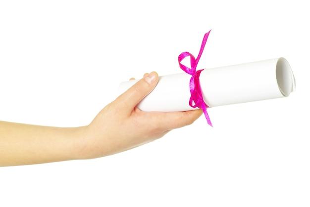 Diploma con una cinta roja en mano aislado en blanco