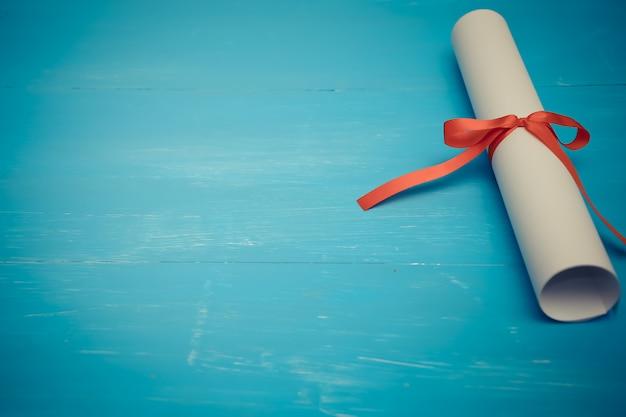 Diploma con cinta roja sobre madera