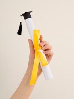 Diploma de graduación con cinta amarilla