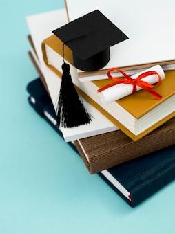 Diploma de graduación con cinta roja y gorro académico en la pila de libros