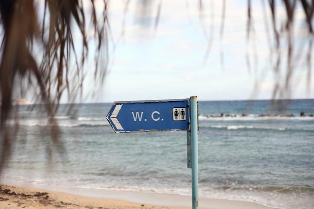 Dirección al baño en la playa. inscripción wc en letrero inodoro colgando de un poste
