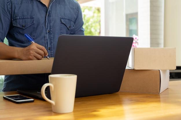 Dirección de la escritura de la mano del hombre de negocios de sme en la caja del paquete con café y el teléfono celular en la tabla