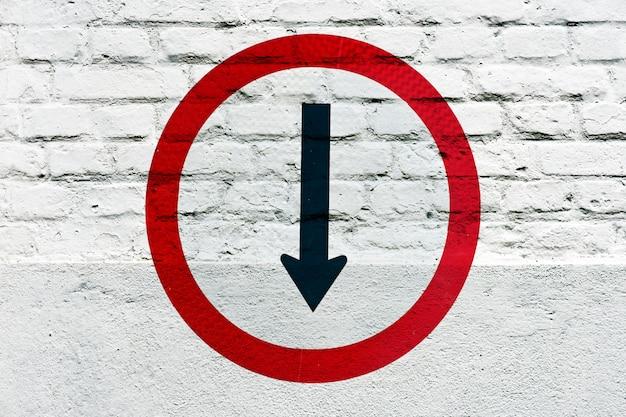 Dirección obligatoria: señal de tráfico estampada en la pared blanca, como graffiti