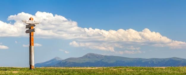 Direcciones de rutas turísticas que se muestran en una señal de dirección tradicional en las montañas.