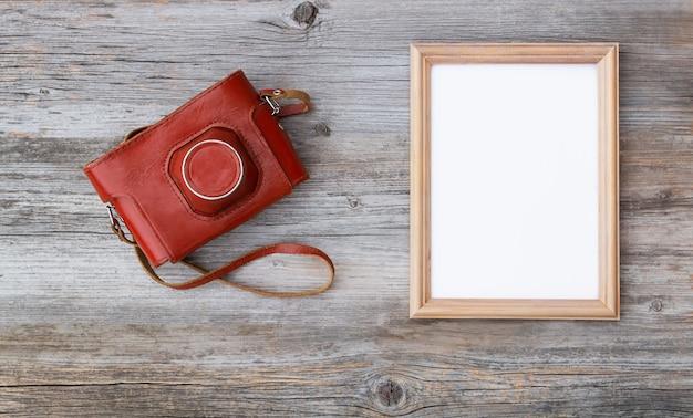 Directamente encima de la toma de un marco en blanco con una cámara retro en una mesa de madera vieja.