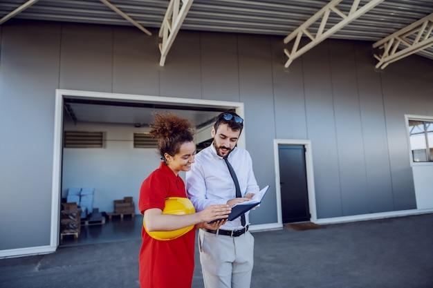 Director alegre mostrando a sus empleadas tareas para el trabajo ese día. el director sostiene el cuaderno y ambos lo están mirando. imprenta exterior.