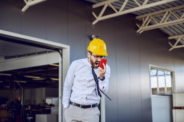 Director caucásico enojado en camisa y corbata y con casco en la cabeza gritando
