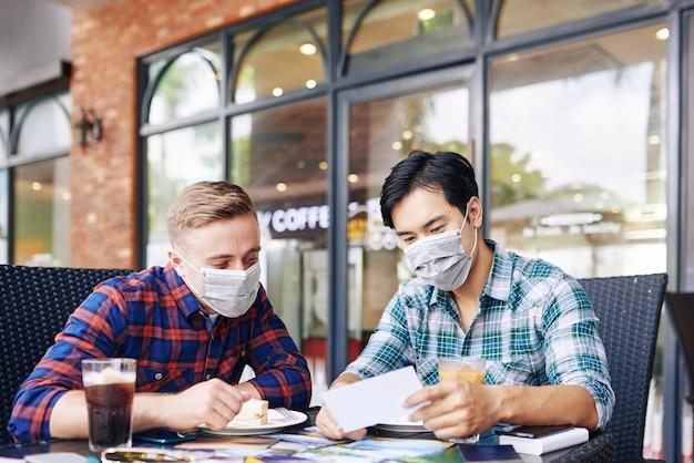 Director de fotografía y proyecto en máscaras médicas reunido en un café al aire libre para almorzar y discutir las fotografías impresas