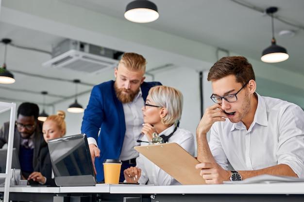 El director masculino da instrucciones a los empleados en la oficina, el equipo joven se sienta a trabajar juntos, usando una computadora portátil y papeles