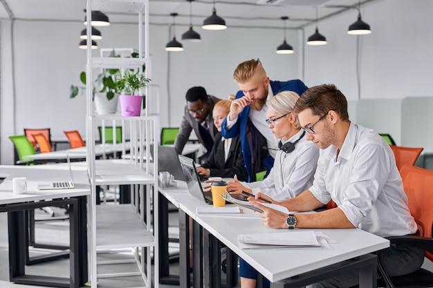 Director masculino da instrucciones a los empleados en la oficina