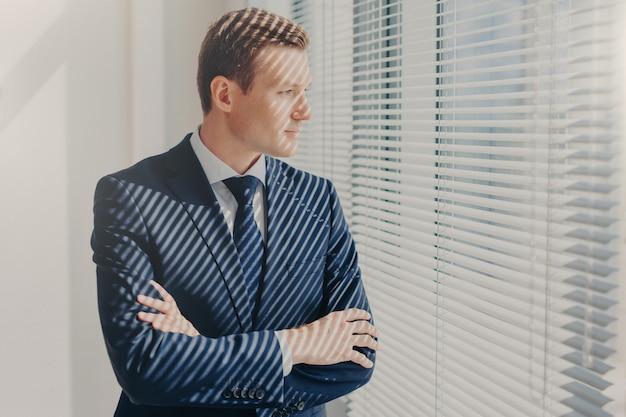El director masculino mantiene los brazos cruzados, piensa en planes de trabajo futuros