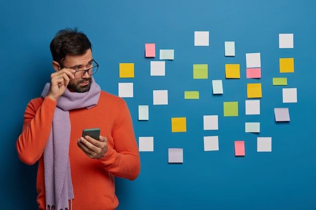 El director masculino serio y atento mira a través de gafas pequeñas notas coloridas en blanco pegadas en la pared azul, estudia información, utiliza un moderno dispositivo electrónico