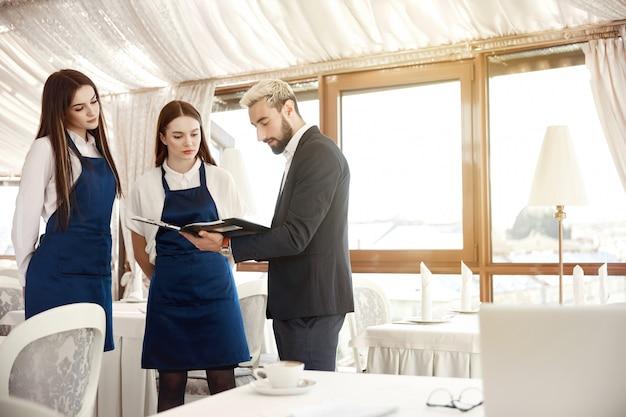 El director de un restaurante está dando instrucciones de trabajo a las camareras.