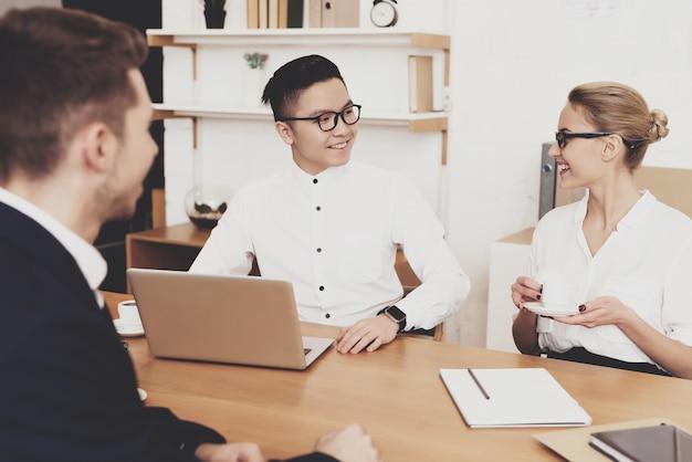 Directora de recursos humanos mujer está trabajando en la oficina. los compañeros de trabajo están mirando la computadora portátil en la entrevista de trabajo.