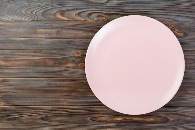 Directy arriba plato mate rosado vacío para la cena sobre fondo de madera oscura con espacio de copia