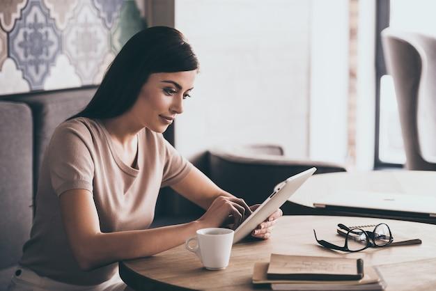 Dirigiendo su nuevo negocio. vista lateral de la joven y bella mujer con su tableta digital mientras está sentado en el café