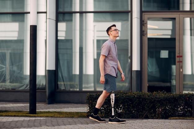 Discapacitado joven con prótesis de pie camina por la calle.