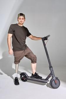 Discapacitado joven con prótesis de pierna con patinete