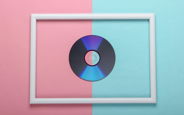 Disco cd en marco blanco sobre superficie pastel azul rosa
