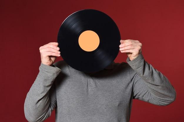 Disco de música cubre su rostro sobre fondo rojo.