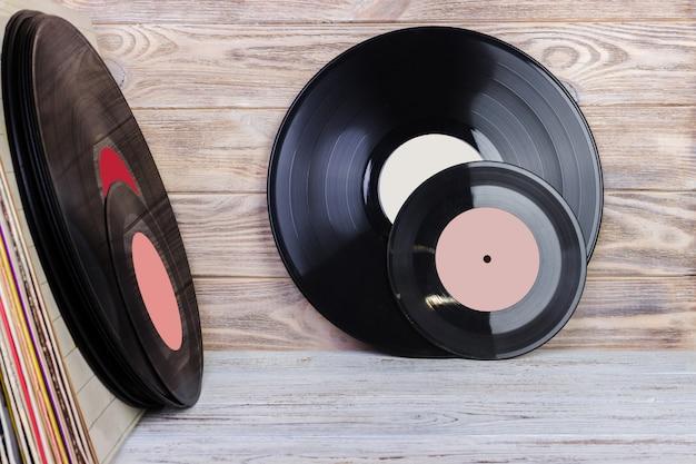 Disco de vinilo frente a una colección de álbumes, proceso vintage.