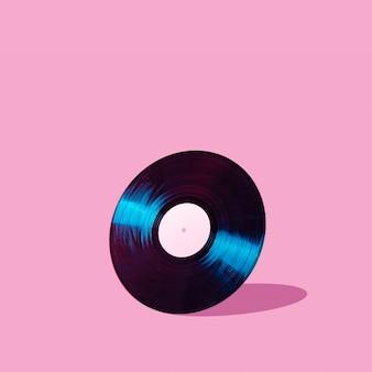Disco de vinilo lp negro aislado sobre fondo rosa pastel abstracto con sombra y espacio de copia