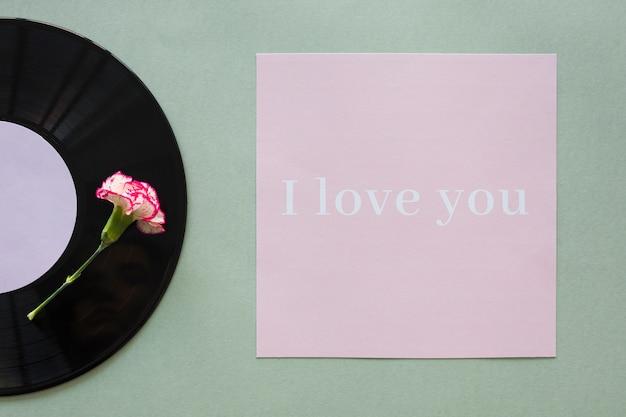 Disco de vinilo negro con inscripción i love you sobre mesa.