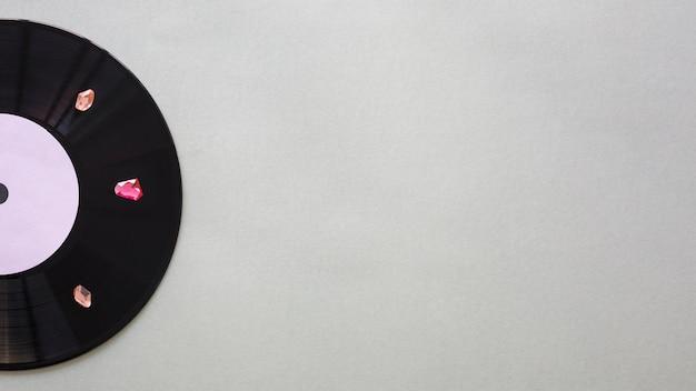 Disco de vinilo negro con piedras preciosas.