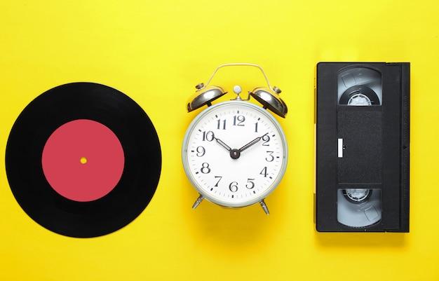 Disco de vinilo retro, antiguo despertador, cinta de video sobre un fondo amarillo. 80s. vista superior. minimalismo