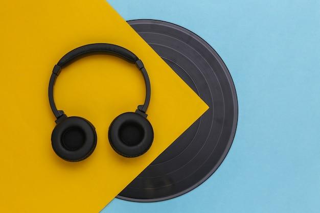 Disco de vinilo retro y auriculares estéreo sobre fondo azul amarillo. vista superior. endecha plana