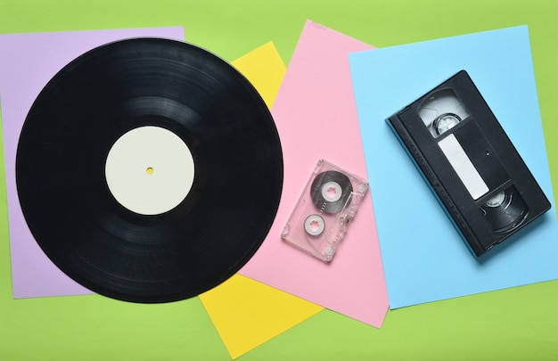 Disco de vinilo, videocasete, videocasete en una pared de papel multicolor. estilo retro. vista superior