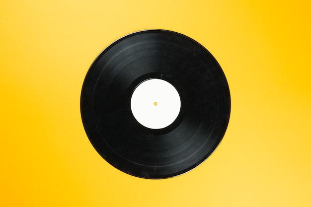 Disco de vinilo vintage con etiqueta blanca vacía sobre fondo naranja. tecnología de sonido retro para reproducir música