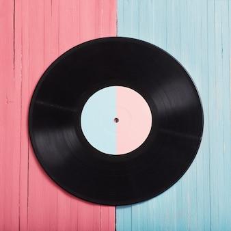 Discos de música sobre fondo de madera rosa y azul. concepto de música retro