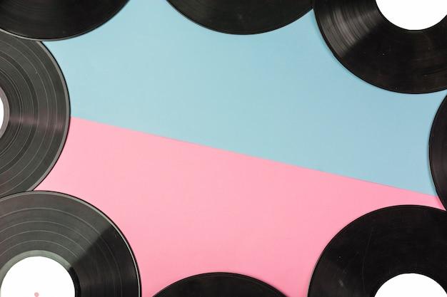 Discos de vinilo bordean sobre doble fondo azul y rosa.