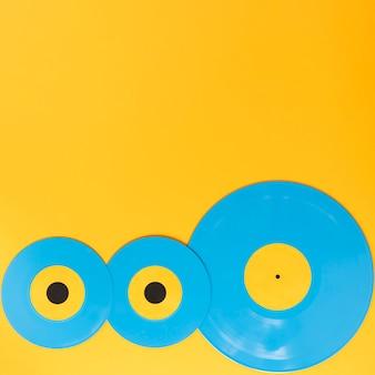 Discos de vinilo sobre fondo amarillo con espacio de copia
