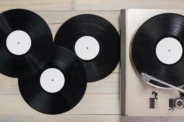 Discos de vinilo y tocadiscos giradiscos en mesa de madera.