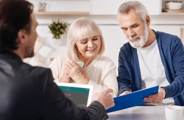 Discutiendo todos los detalles. atento alegre pareja de ancianos concentrados sentados en casa y concluyendo un acuerdo con el asesor inmobiliario mientras lee el contrato con atención