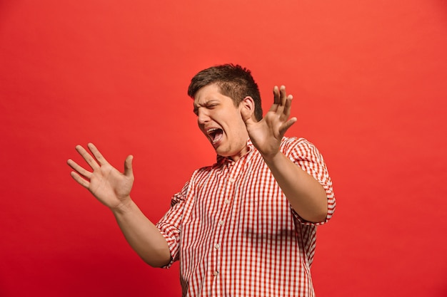 Discutir, argumentar concepto. retrato de medio cuerpo masculino divertido aislado en el fondo de color rojo del estudio. joven sorprendido emocional mirando a cámara. las emociones humanas, el concepto de expresión facial. vista frontal