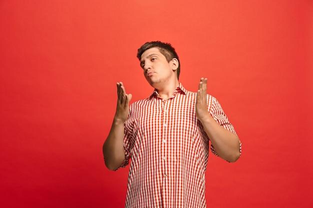Discutir, argumentar concepto. retrato de medio cuerpo masculino divertido aislado sobre fondo rojo de estudio. joven sorprendido emocional