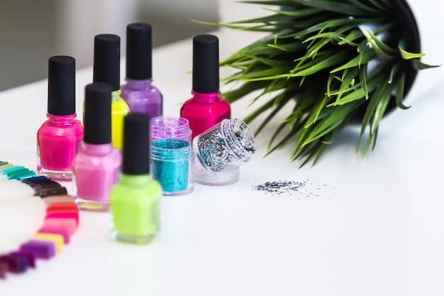 Diseñado para el diseño de manicura: muchos esmaltes de uñas de colores y destellos / brillos en el primer plano de la mesa blanca.