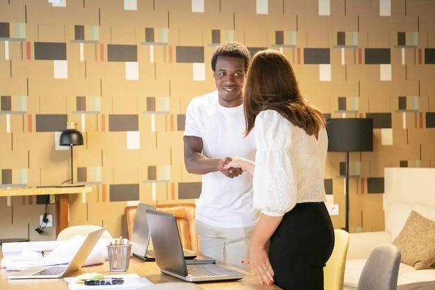 Diseñador afroamericano sonriendo y saludando a la clienta