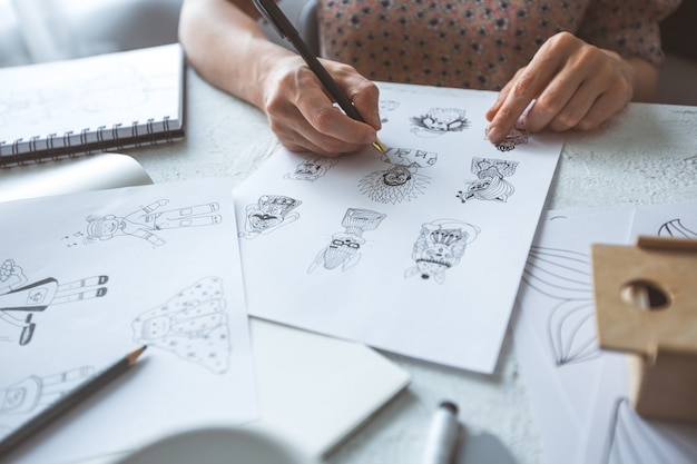 Diseñador animador dibuja bocetos de varios personajes.