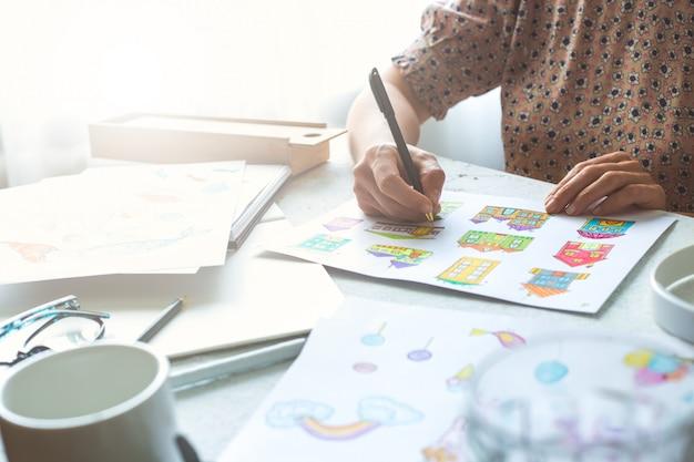 Diseñador animador dibuja coloridos bocetos de varios personajes.
