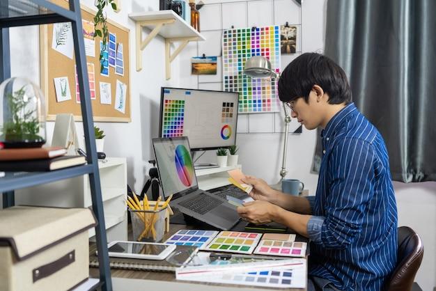 Diseñador asiático o artista de estudio de diseño de ocupación creativa que trabaja en una computadora gráfica en la oficina