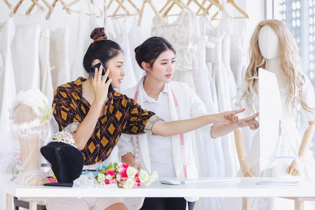 Diseñador asiático trabajando en una tienda de moda nupcial.